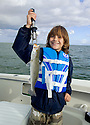Happy child standing in a boat in Chokoloskee Bay holding a trout he just caught. File # D3DW5369