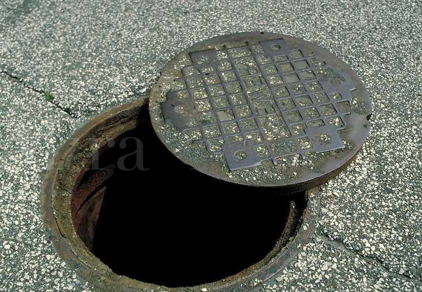 Manhole cover partially removed from a manhole.  May not be used in an elementary school dictionary. Cleveland Ohio USA.