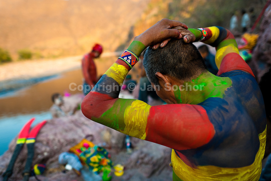 """A Cora Indian man, painting his body in colors, prepares himself for the religious ritual ceremony of Semana Santa (Holy Week) in Jesús María, Nayarit, Mexico, 22 April 2011. The annual week-long Easter festivity (called """"La Judea""""), performed in the rugged mountain country of Sierra del Nayar, merges indigenous tradition (agricultural cycle and the regeneration of life worshipping) and animistic beliefs with the Christian dogma. Each year in the spring, the Cora villages are taken over by hundreds of wildly running men. Painted all over their semi-naked bodies, fighting ritual battles with wooden swords and dancing crazily, they perform demons (the evil) that metaphorically chase Jesus Christ, kill him, but finally fail due to his resurrection. La Judea, the Holy Week sacred spectacle, represents the most truthful expression of the Coras' culture, religiosity and identity."""