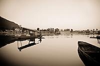 Sepia toned photograph of Shikara, or gondola boat, on a mirroe calm Dal Lake, Srinagar, Kashmir, India.