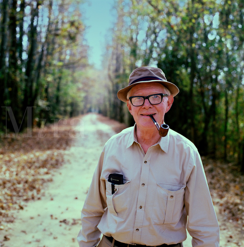 Man smoking his pipe as he walks along a country road. Tom Harding. Arkansas.