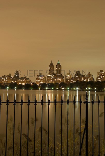 AVAILABLE FROM JEFF AS A FINE ART PRINT.<br /> <br /> AVAILABLE FROM PLAINPICTURE FOR COMMERCIAL AND EDITORIAL LICENSING.  Please go to www.plainpicture.com and search for image # p5690193.<br /> <br /> Manhattan's Upper West Side on an Overcast Night, Viewed Thru Cast Iron Fence Surrounding the Central Park Reservoir, New York City, New York State, USA
