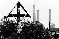 """Poland. Silesia. Bobrek. Jesus Christ on the wooden Holy Cross. """" Hutta Bobrek """" is the factory's name. Major polluted area due to old iron and steel works and heavy metals supended in the air. Bobrek is a small town, distant 20 km from Katowice. © 1991 Didier Ruef"""