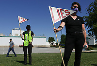 Protestors hold up signs, Friday, May 29, 2020 during a protest rally at George's Hatchery Plant in Springdale. A poultry workers' rights group, Venceremos, hosted a rally and car caravan to protest how workers are being treated in relation to covid-19. Check out nwaonline.com/200530Daily/ for today's photo gallery. <br /> (NWA Democrat-Gazette/Charlie Kaijo)