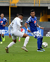BOGOTA - COLOMBIA, 18-04-2021: Fernando Uribe de Millonarios F. C. y Jorge Marsiglia de Deportivo Cali disputan el balon durante partido entre Millonarios F. C. y Deportivo Cali de la fecha 19 por la Liga BetPlay DIMAYOR I 2021 jugado en el estadio Nemesio Camacho El Campin de la ciudad de Bogota. / Fernando Uribe of Millonarios F. C. and Jorge Marsiglia of Deportivo Cali figth for the ball during a match between Millonarios F. C. and Deportivo Cali of the 19th date for the BetPlay DIMAYOR I 2021 League played at the Nemesio Camacho El Campin Stadium in Bogota city. / Photo: VizzorImage / Luis Ramirez / Staff.