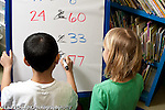 "Education Elementary school Grade 1 mathematics dry erase board with ""greater than"" ""less than"" activity two students working one boy and one girl horizontal"