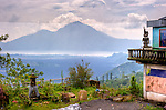 A Balinese home and its yard (featuring a small Hindu altar) provide a spectacular overlook of the Mount Batur volcano and Batur crater lake.  Bali's spectacular Mount Batur volcano and crater lake frame the view of countryside from the high road climbing the ridge line originally formed by the rim of the volcano's caldera, traveling from the north coast south to Ubud.  This angle features Batur lake framed by Bali's tallest mountain, Agung, in the background.  (Bali, Indonesia; HDR image)