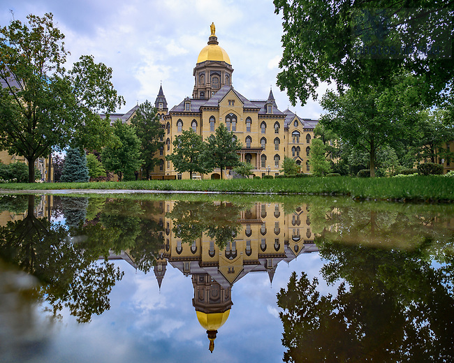 July 13, 2021; Main Building reflected in a puddle after a summer rain shower (Photo by Matt Cashore/University of Notre Dame)