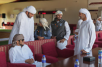 United Arab Emirates (UAE). Abu Dhabi. Organised jointly by the Hamdan Bin Mohammed Center for the Revival of Heritage (HHC) and Abu Dhabi Falconers Club, the UAE Falconers League has a total of nine rounds that ran until February 19 between Dubai and Abu Dhabi. Humaid Al Tayer (C) with his his son is a rich Emirati man with a passion for falcons. He is the owner of A&H Falcons which take parts in various falcons' competitions. He is joking with his friends before the start of falcons' races. All men wear a thawb (thobe, dishdasha, kandora) which is an ankle-length garment, usually with long sleeves, similar to a robe, kaftan or tunic, commonly worn in the Arabian Peninsula. The traditional headdress is called ghutrah. Falcons are birds of prey in the genus Falco, which includes about 40 species. Adult falcons have thin, tapered wings, which enable them to fly at high speed and change direction rapidly. Additionally, they have keen eyesight for detecting food at a distance or during flight, strong feet equipped with talons for grasping or killing prey, and powerful, curved beaks for tearing flesh. The United Arab Emirates (UAE) is a country in Western Asia at the northeast end of the Arabian Peninsula. 18.02.2020  © 2020 Didier Ruef