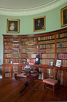 A curved bookcase contains many antique volumes in the green library