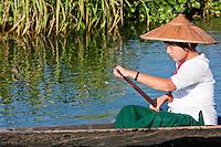 Myanmar, Burma.  Young Burmese Girl of Intha Ethnic Group Paddling her Canoe, Inle Lake, Shan State.