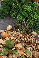 Bunches of bananas and piles of coconuts at city fruit market, Male, Maldives.