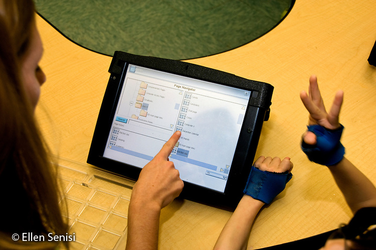 MR / Albany, NY.Langan School at Center for Disability Services .Ungraded private school which serves individuals with multiple disabilities.Screen of alternative and augmentative communication device on classroom table that is being used by student during speech and language development lesson. Screen shows navugation menu of device. Student is wearing hand splints to help him isolate his thumbs, which will make it easier for him to use this device. Boy: 8, cerebral palsy, spastic quadriplegic, nonverbal with expressive and receptive language delays.MR: Rub1.© Ellen B. Senisi