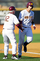 Nick O'Shea #23 of the Minnesota Golden Gophers shakes hands with John Anderson as he rounds third base following his 2-run home run against the Towson Tigers at Gene Hooks Field on February 26, 2011 in Winston-Salem, North Carolina.  The Gophers defeated the Tigers 6-4.  Photo by Brian Westerholt / Four Seam Images