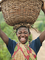 A woman laughs while carrying a wicker basket on her head, Rwanda