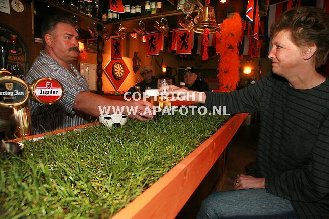 arnhem 190506 In Cafe Klein Royal in het arnhemse Klarendal is de bar in het kader van het WK bedekt met echt gras. het wordt 1x per week ivm gemorst bier, vervangen, daardoor hoeft het niet gemaaid te worden. Barman Frans Peters proost met een van de bezoekers op de goede afloop voor nederland.<br />Foto frans Ypma APA-foto