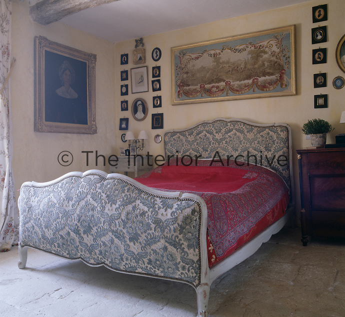 An upholstered Louis XVI bed occupies a corner of a simple bedroom with a stone floor