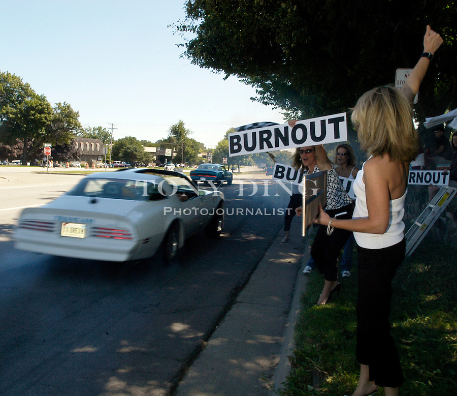 """The Williams sisters, Kristy (center), from Metamora, Mich. hold up large """"Burnout"""" signs to try to entice cruisers on Woodward Ave. to stop in front of them and burn rubber, during the 10th Anniversary Woodward Dream Cruise, on Saturday, August 21, 2004, in Pontiac, MI. (Photo by TONY DING)."""