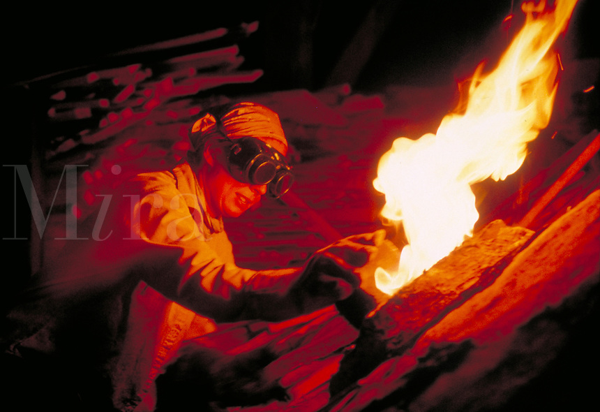A ceramicist works on a kiln. Flames come from the kiln. Ceramics. Firing. Worker. Craftsperson. Artisan. People. Clay. Ceramicist. New Jersey.