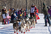 Joar Leifseth Ulsom and team run past spectators on the bike/ski trail during the Anchorage ceremonial start during the 2014 Iditarod race.<br /> Photo by Britt Coon/IditarodPhotos.com