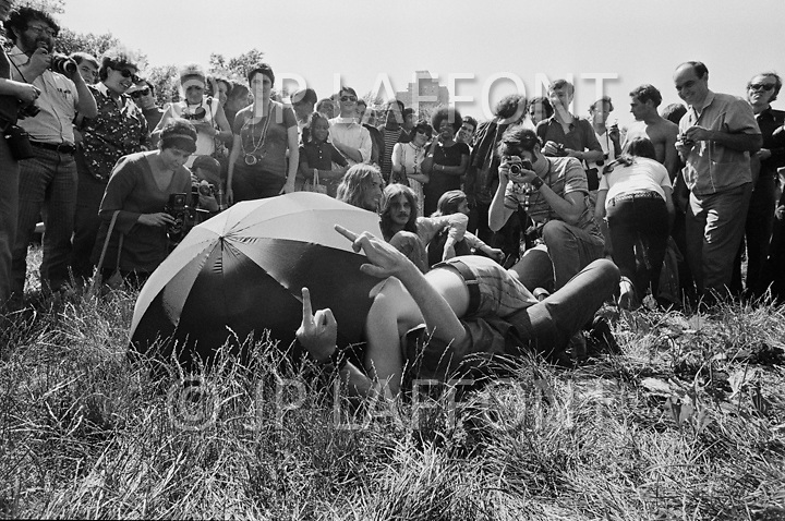 Manhattan, New York City, NY. 28 Jun 1970. <br /> Two men flip the bird to the gathering crowd in Central Park as the two lie on the ground and kiss for the kissing contest during New York's first Gay Pride celebration.