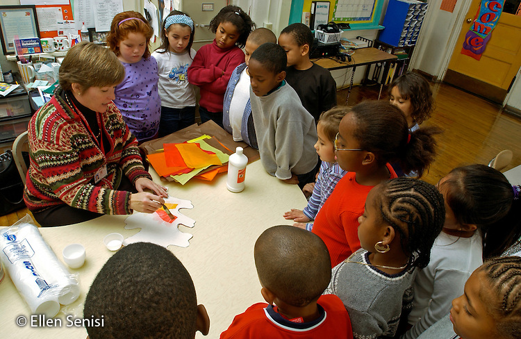 MR / Schenectady, NY. Yates Arts in Education Magnet School, Grade 2.Arts-Themed Urban Elementary School.Teacher gives directions to students for doing in-class art project on fall colors using tissue paper and glue..MR: g2c.© Ellen B. Senisi