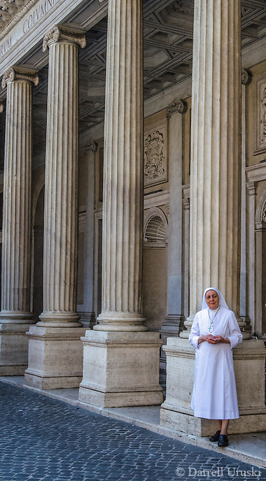 Urban Street Photography. A Roman Catholic Nun stands beside one of the tall columns in the piazza colonna plaza.