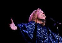 """Isabelle Aubray in concert, circa 1986<br /> <br /> ThÈrËse Coquerelle dite Isabelle Aubret<br /> <br /> NÈe le 27 juillet 1938 ? Lille<br /> <br /> Bobineuse mais Ègalement gymnaste de talent (elle dÈcroche le titre de championne de France en 1952), ThÈrËse Coquerelle, qui ne tardera pas ? se faire appeler Isabelle Aubret, montre par ailleurs des prÈdispositions pour la chanson.<br /> Au dÈbut des annÈes 60, elle se produit dans des orchestres avant de se retrouver sur la scËne de l'Olympia ? la faveur d'un concours. Bruno Coquatrix, le maÓtre des lieux, qui la remarque, lui permet d'effectuer ses vÈritables dÈbuts dans un cabaret parisien, le Fifty-Fifty.<br /> Autre rencontre dÈterminante pour Isabelle Aubret, celle qu'elle fait avec Jacques Canetti, dÈcouvreur de talents, notamment Charles Aznavour ou encore Edith Piaf. L'agent artistique lui fait enregistrer son premier 45 tours, signÈ Maurice Vidalin. Et en 1962 c'est la consÈcration au concours de l'Eurovision avec """" Un premier amour """".<br /> <br /> La rencontre avec Ferrat<br /> <br /> C'est cette m?me annÈe qu'elle se lie d'une amitiÈ, qui s'avËrera sans faille, avec Jean Ferrat, qui lui Ècrit """" Deux enfants au soleil """". Il lui propose Ègalement la premiËre de sa tournÈe.<br /> DÈcidemment trËs sollicitÈe, Isabelle Aubret est en premiËre partie de Jacques Brel ? l'Olympia. Toujours en 1963, elle est aux cÙtÈs de Sacha Distel.<br /> Elle est Ègalement appelÈe par Jacques Demy et Michel Legrand qui travaillent sur """" Les parapluies de Cherbourg """" et entendent lui confier le rÙle principal. Le projet ne se concrÈtisera jamais, du moins pour Isabelle Aubret qui est victime d'un dramatique accident de la route qui lui voudra une quinzaine d'interventions chirurgicales et des annÈes de rÈÈducation.<br /> En 1964, la chanteuse, qui ne manque pas de volontÈ, revient ? la chanson ? la faveur de """" C'est beau la vie """", Ècrite par Jean Ferrat. Un titre qui lui vaut un large succËs un an plus tard.<br /> Toujours en rÈÈd"""