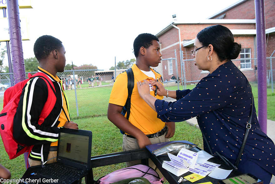 Seventh grader Isaac Friels gets a nametag and greets Principal Liza Jacobs at Marksville High School in Marksville, La., Sept. 18, 2017.
