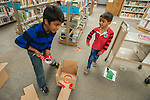 Sohan Vadlakunta, left, and his brother Sathvik Vadlakunta help build an obstacle during the Mini Golf Night at the Carson City Library on Friday May 9, 2014. Kids and parents built a custom mini golf course throughout the library using anything at their disposal and engineering ideas to make a difficult course. Everything from tables to shelves were used to create creative courses.<br /> (Photo by Kevin Clifford/Nevada Photo Source)