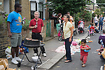 Street party east London ethnic diverse group of neighbours talking chatting, making new friends over a drink and barbecue. 2009.