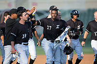 Micker Adolfo (27) of the Kannapolis Intimidators is congratulated by his teammates after his game winning hit in the bottom of the seventh inning against the Hagerstown Suns at Kannapolis Intimidators Stadium on June 15, 2017 in Kannapolis, North Carolina.  The Intimidators walked-off the Suns 5-4 in game one of a double-header.  (Brian Westerholt/Four Seam Images)
