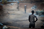 Ouagadougou: in a hidden ground four thousand workers (most women and children) break stones and transform in gravel. Work conditions are very heavy for high temperatures that are over 50 degrees, smoke from burned tyres used to burn stones.