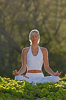 An attractive woman meditates in Makena, Maui.