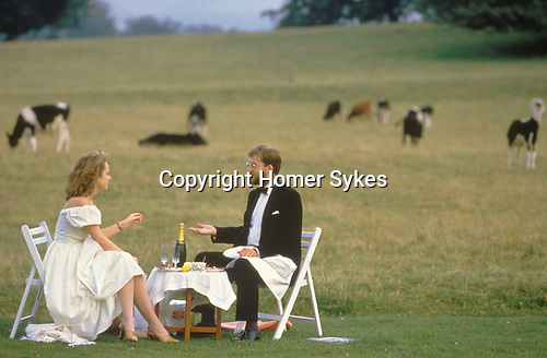 Glynde, East Sussex. 1985<br /> On the ha-ha lawn at Glyndebourne Festival Opera. and in formal evening attire a couple of opera lovers enjoy an alfresco smoked salmon supper and a still unopened bottle of Champagne. They are discussing the merits of the first act of  Mozart's Idomeneo based on a story by Homer.