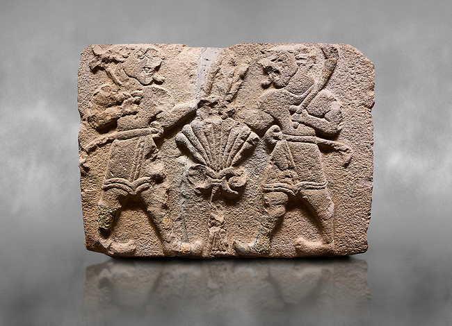 Aslantepe Hittite relief sculpted orthostat stone panel of Lion Men. Limestone, 1399-1301 BC. Anatolian Civilizations Museum, Ankara, Turkey.<br /> <br /> There are two lion-men with a sword at their waists on both sides of the tree of life. The figure on the right holds a sickle in his left hand resting on his shoulder and a symbol his right hand. The figure on the left carries a double-faced ax in his right hand. <br /> <br /> Against a grey art background.