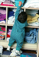 A toddler reaches for an object on a shelf.