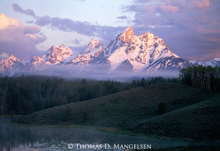 The snow-capped Tetons with fog rising off a pond at sunrise in Grand Teton National Park, Wyoming.