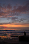 Windansea, La Jolla, California; a couple is silhouette against the ocean at sunset, standing on the rocks at the water's edge