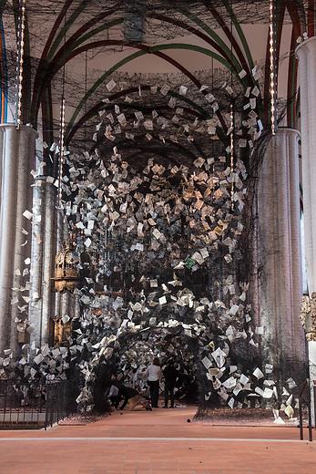 Die Rauminstallation LOST WORDS der 45jaehrigen japanischen Kuenstlerin Chiharu Shiota im Inneren der Berliner Nikolaikirche.<br /> Im Kirchenschiff wurde ein dichtes Gespinst aus ueber 750 Kilometern schwarzen Faeden, mit 4.000 Bibelseiten verschiedener Zeiten und Uebersetzungen sowie ueber 100 Sprachen eingewoben sind. Es steht fuer die Kuenstlerin als ein Sinnbild fuer die globale Verflochtenheit der Reformation und der biblischen Botschaft. Vor dem Hintergrund der Geschichte ihrer Japanischen Heimat verbindet Shiota in der Installation die aktuellen Debatten um Migration und Integration mit der Frage nach dem der Verbreitung der biblischen Schriften, die ihrerseits Teil unseres kulturellen Gedaechtnisses innerhalb einer weltweiten Migrations- und Integrationsgeschichte sind.<br /> Das Kunstwerk ist vom 29. September bis 19. November 2017 in der Nikolaikirche zu sehen.<br /> 28.9.2017, Berlin<br /> Copyright: Christian-Ditsch.de<br /> [Inhaltsveraendernde Manipulation des Fotos nur nach ausdruecklicher Genehmigung des Fotografen. Vereinbarungen ueber Abtretung von Persoenlichkeitsrechten/Model Release der abgebildeten Person/Personen liegen nicht vor. NO MODEL RELEASE! Nur fuer Redaktionelle Zwecke. Don't publish without copyright Christian-Ditsch.de, Veroeffentlichung nur mit Fotografennennung, sowie gegen Honorar, MwSt. und Beleg. Konto: I N G - D i B a, IBAN DE58500105175400192269, BIC INGDDEFFXXX, Kontakt: post@christian-ditsch.de<br /> Bei der Bearbeitung der Dateiinformationen darf die Urheberkennzeichnung in den EXIF- und  IPTC-Daten nicht entfernt werden, diese sind in digitalen Medien nach §95c UrhG rechtlich geschuetzt. Der Urhebervermerk wird gemaess §13 UrhG verlangt.]