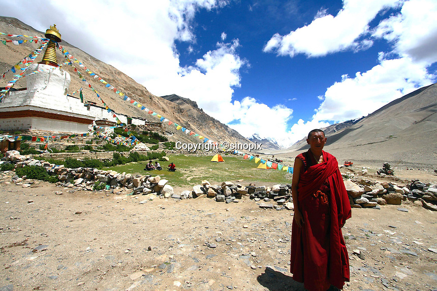 """China started building a controversial 67-mile """"paved highway fenced with undulating guardrails"""" to Mount Qomolangma, known in the west as Mount Everest, to help facilitate next year's Olympic Games torch relay./// Monk Lobsang Cheodeng  stands in front of Rongbuk Monastery near Everest base camp."""