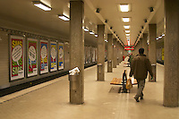 The Stockholm underground subway Tunnelbanan Tunnelbana an empty platform at the station Radmansgatan and concrete pillars a man walking with a plastic bag in his hand publicity posters on the walls Stockholm, Sweden, Sverige, Europe