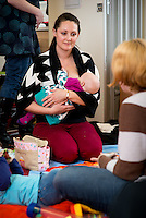 """A mother breastfeeds her baby while talking to another mother at a drop-in breastfeeding support centre.<br /> <br /> Image from the breastfeeding collection of the """"We Do It In Public"""" documentary photography picture library project: <br />  www.breastfeedinginpublic.co.uk<br /> <br /> Hampshire, England, UK<br /> 13/03/2013<br /> <br /> © Paul Carter / wdiip.co.uk"""