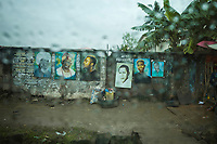 Nigeria. Lagos. Art shop. Local artist is selling framed painting on a rainy day. (Left) Akinwande Oluwole Babatunde Soyinka (born 13 July 1934), known as Wole Soyinka, is a Nigerian playwright, poet and essayist. He was awarded the 1986 Nobel Prize in Literature, the first African to be honoured in that category. (Second left) Bola Ahmed Adekunle Tinubu (born 29 March 1952) is a Nigerian politician who was elected senator for the Lagos West Constituency. He has been routinely referred to as the national leader of the APC during the presidency of Muhammadu Buhari. (Fourth left) Barack Hussein Obama ( born August 4, 1961) is an American attorney and politician who served as the 44th president of the United States from 2009 to 2017. A member of the Democratic Party, he was the first African American to be elected to the presidency. (Sixth from left) Ayodeji Ibrahim Balogun (born 16 July 1990), known professionally as Wizkid (sometimes stylized as WizKid), is a Nigerian singer and songwriter. Lagos is a city in the Nigerian state of the same name. The city, with its adjoining conurbation, is the most populous in Nigeria and on the African continent. It is one of the fastest growing cities in the world and one of the most populous urban areas. 26.06.19 © 2019 Didier Ruef
