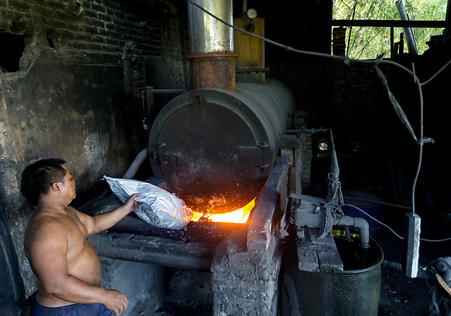 21 May 2019, Klagen Tropodo, East Java, Indonesia: A local man feeds plastic fuel in to a furnace at a factory producing tofu at Klagen Tropodo village outside Surabaya, Indonesia. Millions of tonnes of recyclable plastic trash from Australia and Europe is dumped for rag pickers to separate and sort. The plastics are used to fuel fires at local tofu factories among other industries. Australia is illegally sending non recyclable trash hidden within this lode and the Indonesian Government is cracking down on the practice and preparing to refuse to take Australia's rubbish that is creating environmental and health issues locally. Picture by Graham Crouch/The Australian