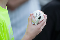 A young Charlotte Knights fan holds a baseball signed by Tyler Saladino (8) of the Charlotte Knights prior to the exhibition game against the Chicago White Sox at BB&T Ballpark on April 3, 2015 in Charlotte, North Carolina.  The Knights defeated the White Sox 10-2.  (Brian Westerholt/Four Seam Images)