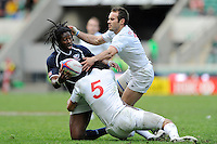 Justin Boyd of the United States is tackled by Paul Albaladejo and Renaud Delmas of France (right) during the iRB Marriott London Sevens at Twickenham on Sunday 13th May 2012 (Photo by Rob Munro)