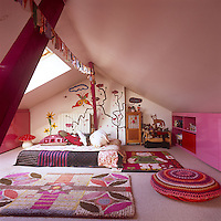 An attic bedroom in shades of pink and a painted mural on one wall. Floral pattern rugs and a crochet cushion surround the bed.