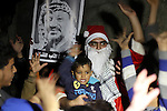 A Palestinian man in Santa Claus costume poses for a picture after distributing gifts to children as part of Christmas and New Year festivities, in Shijaiyah neighborhood, east Gaza, on December 31, 2014. Photo by Mohammed Asad