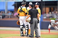 Beer City Tourists catcher Robbie Perkins (11), starting pitcher Brandon Gold (18) and pitching coach Ryan Kibler (9) have a discussion as home plate umpire Aaron Schorch lets them their time is up during a game against the Lakewood BlueClaws at McCormick Field on June 1, 2017 in Asheville, North Carolina. The Tourists defeated the BlueClaws 8-5. (Tony Farlow/Four Seam Images)